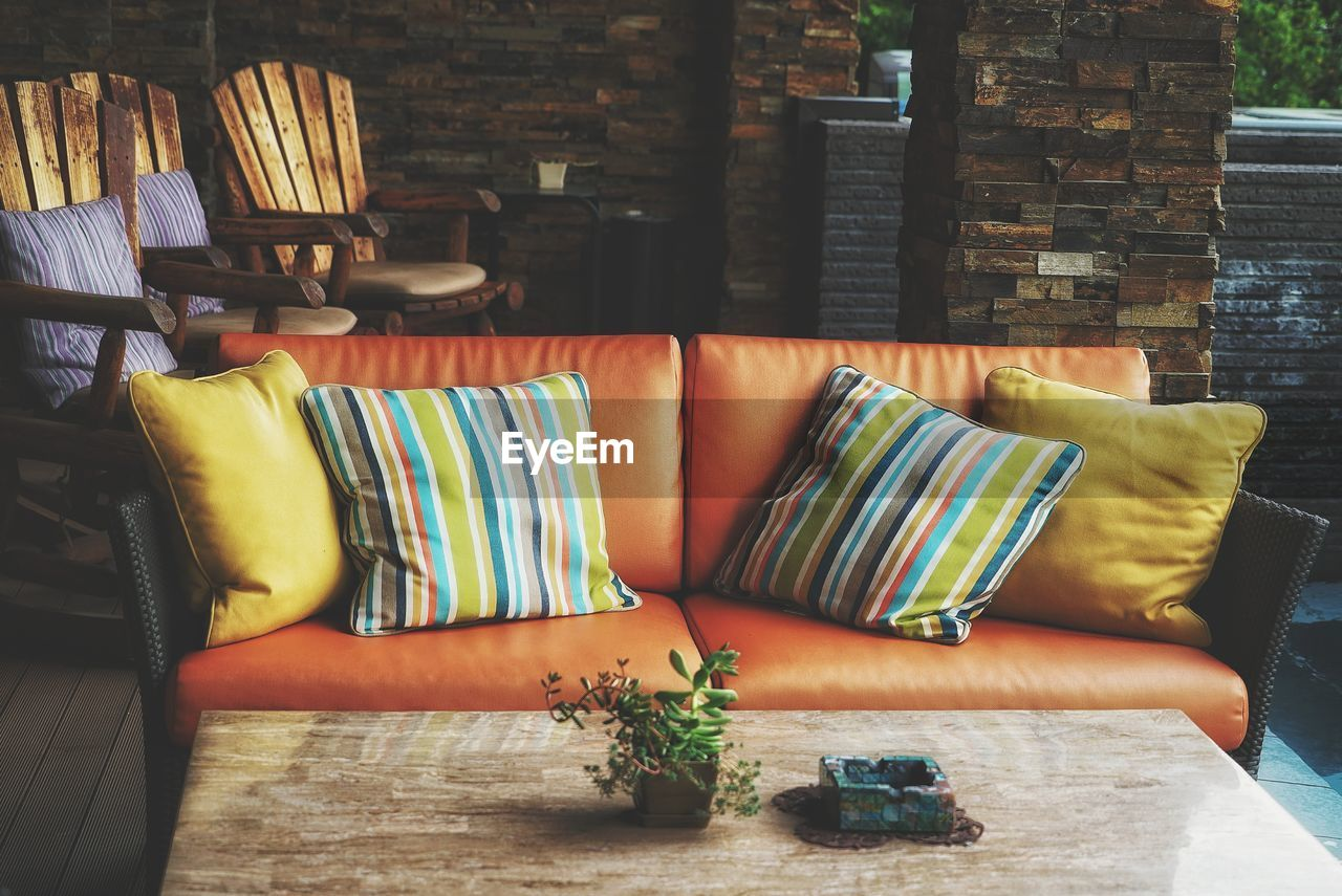 Table by sofa with cushions at porch