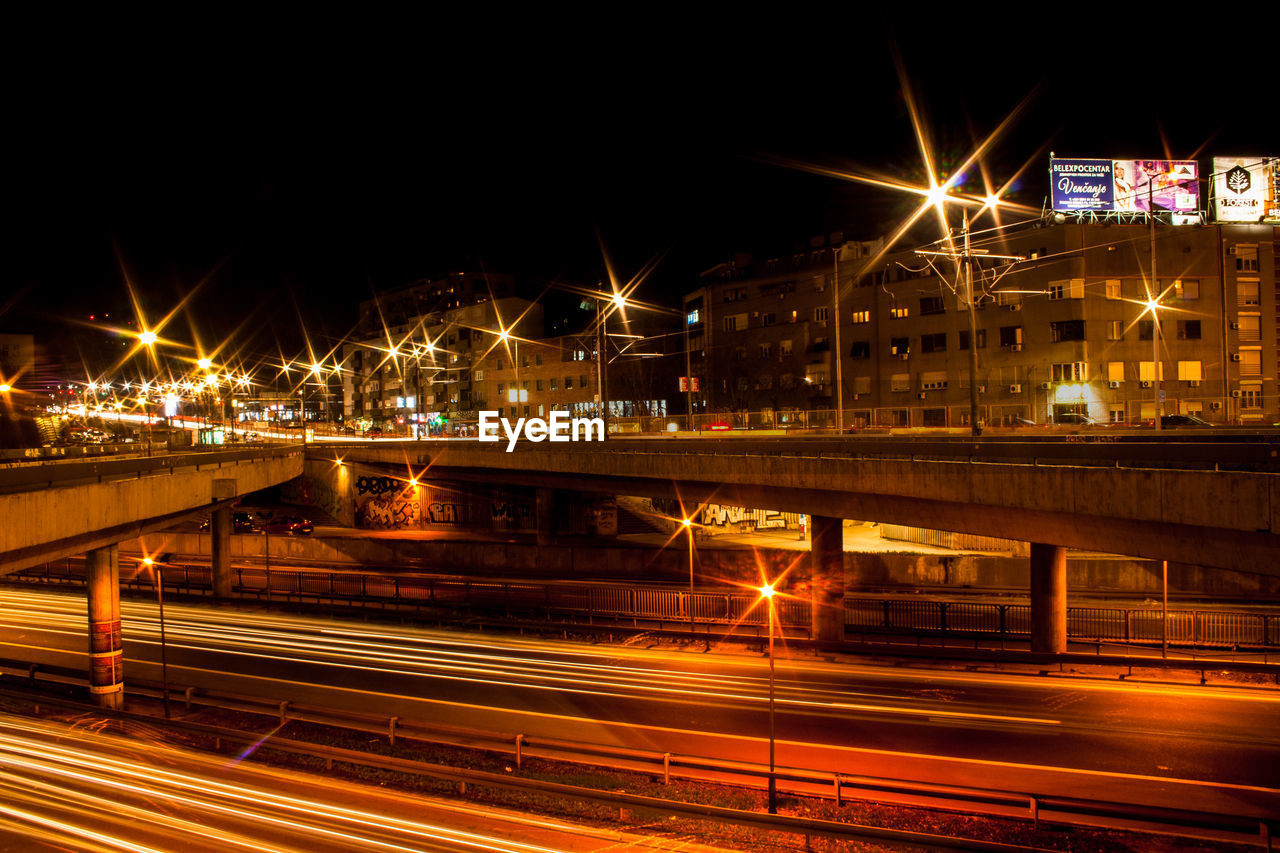 illuminated, night, transportation, built structure, architecture, bridge - man made structure, building exterior, street light, long exposure, city, light trail, motion, outdoors, no people, sky