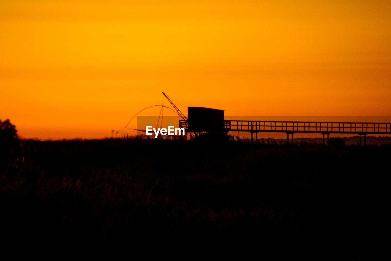 Silhouette Cranes Against Orange Sky