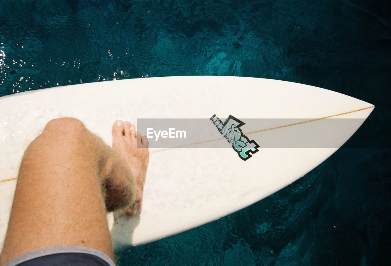 one person, leisure activity, real people, lifestyles, relaxation, human body part, low section, high angle view, water, body part, human leg, personal perspective, unrecognizable person, pool, adult, indoors, directly above, day, swimming pool, human foot