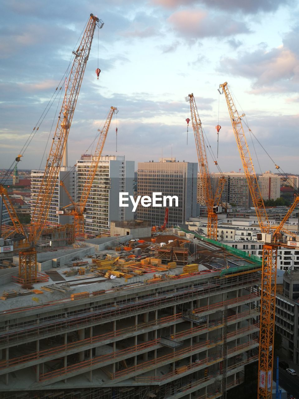 Cranes at construction site against sky in city