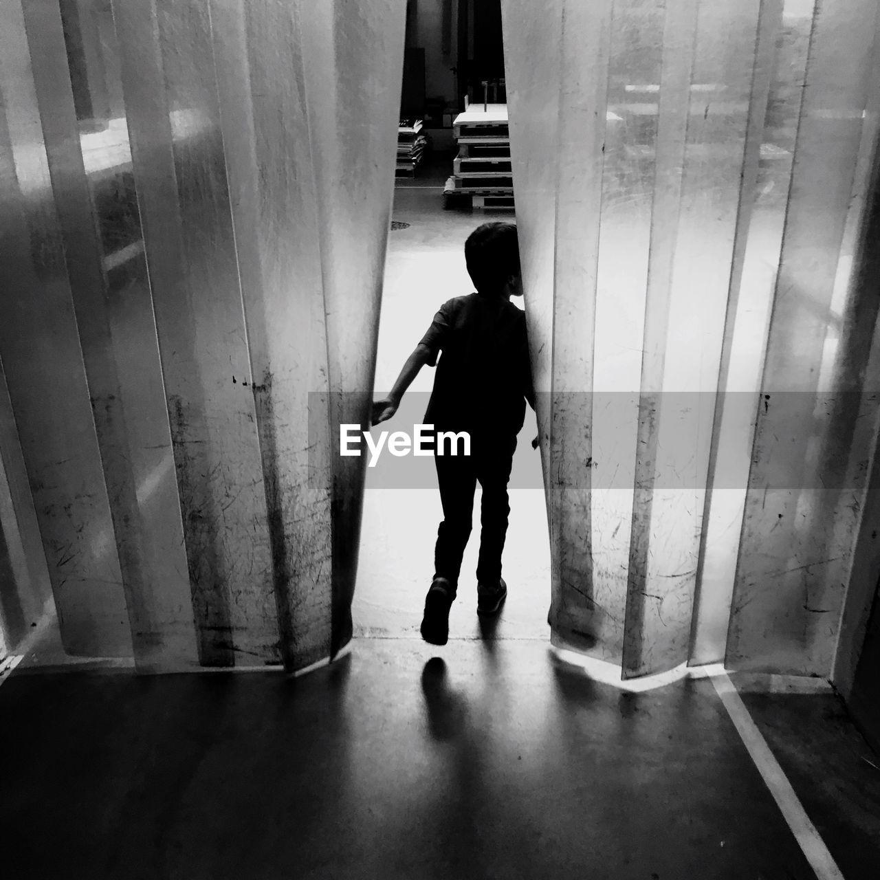 FULL LENGTH REAR VIEW OF MAN WALKING IN CORRIDOR