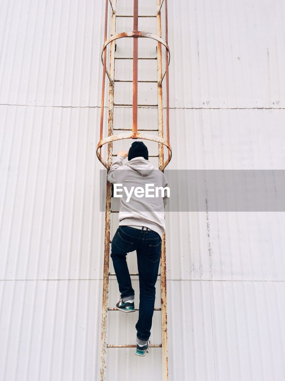 Rear view full length of man climbing on rusty ladder by white wall