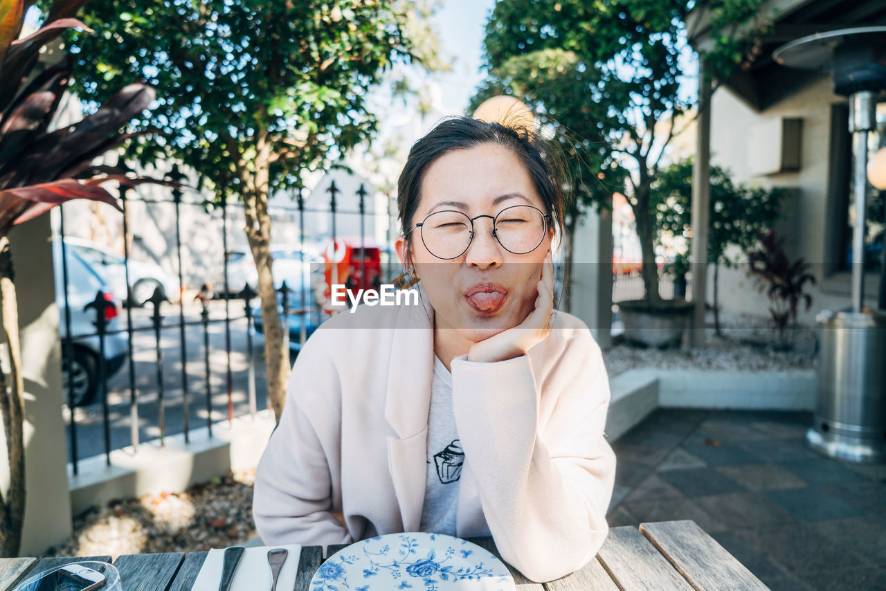 Woman Sticking Out Tongue While Sitting At Table