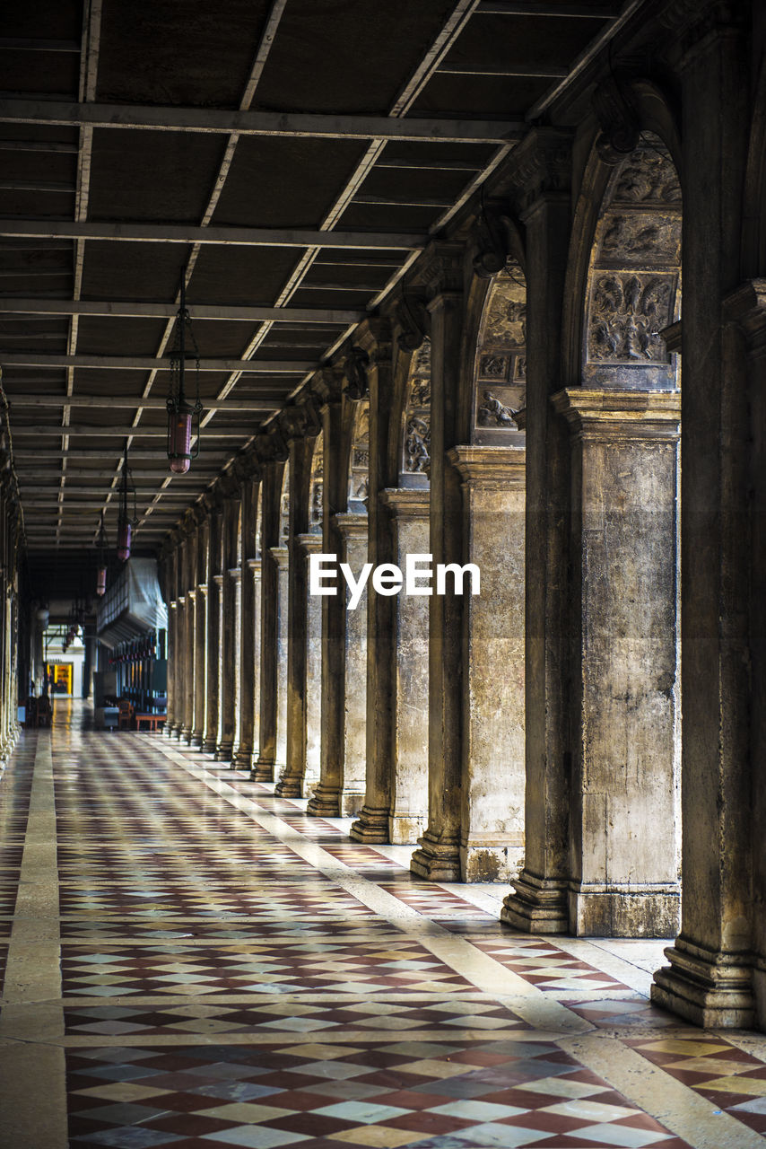 architectural column, architecture, built structure, arcade, indoors, arch, building, colonnade, in a row, corridor, day, the past, no people, direction, the way forward, history, empty, sunlight, flooring, ceiling, tiled floor