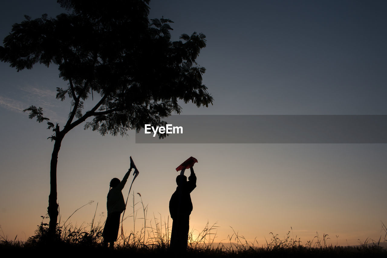 Silhouette children with arms raised against sky during sunset
