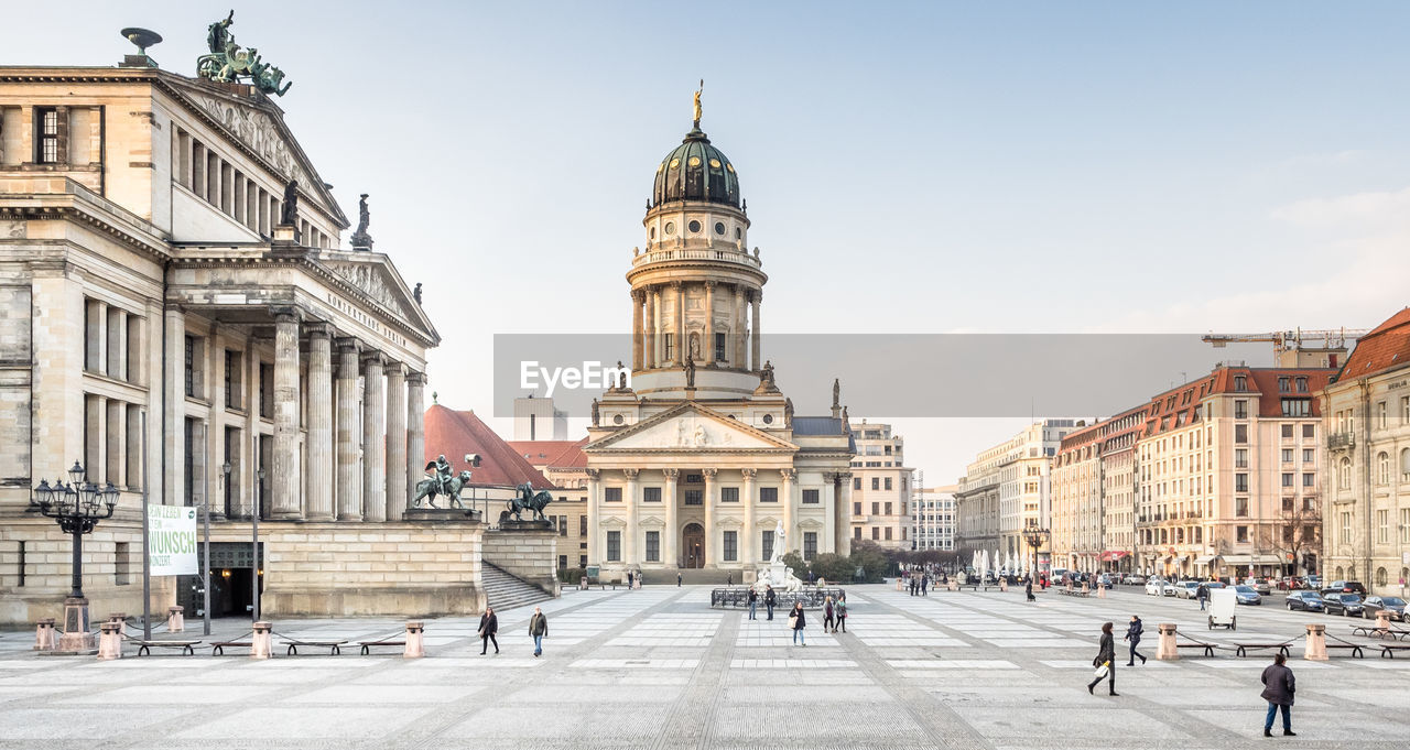 People Walking By French Cathedral At Gendarmenmarkt