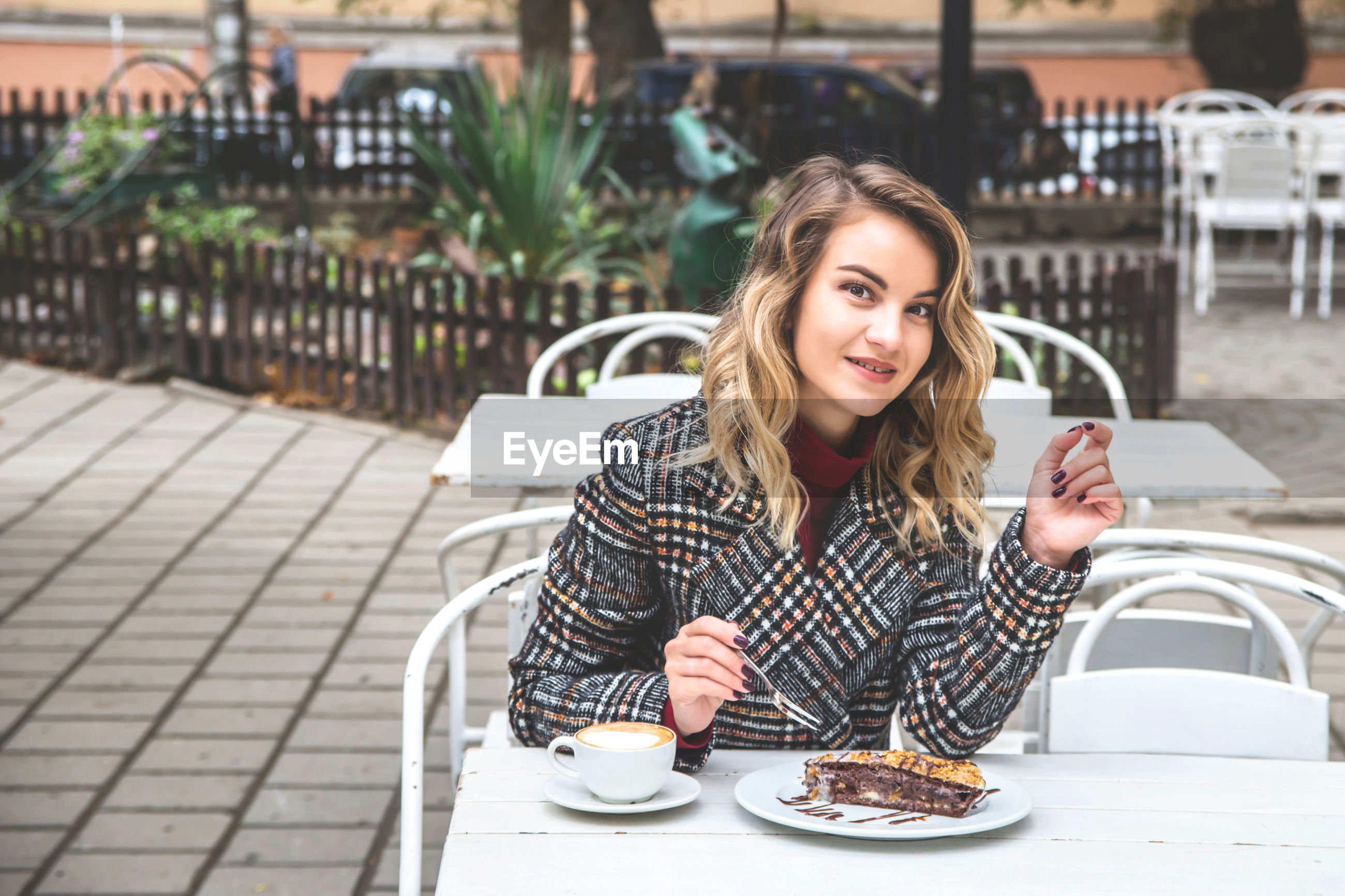 Portrait of young woman having dessert with coffee at outdoor cafe