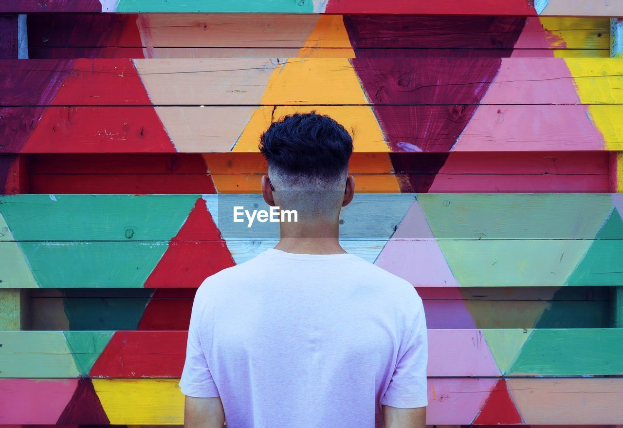 Man Standing In Front Of Multi Colored Wall