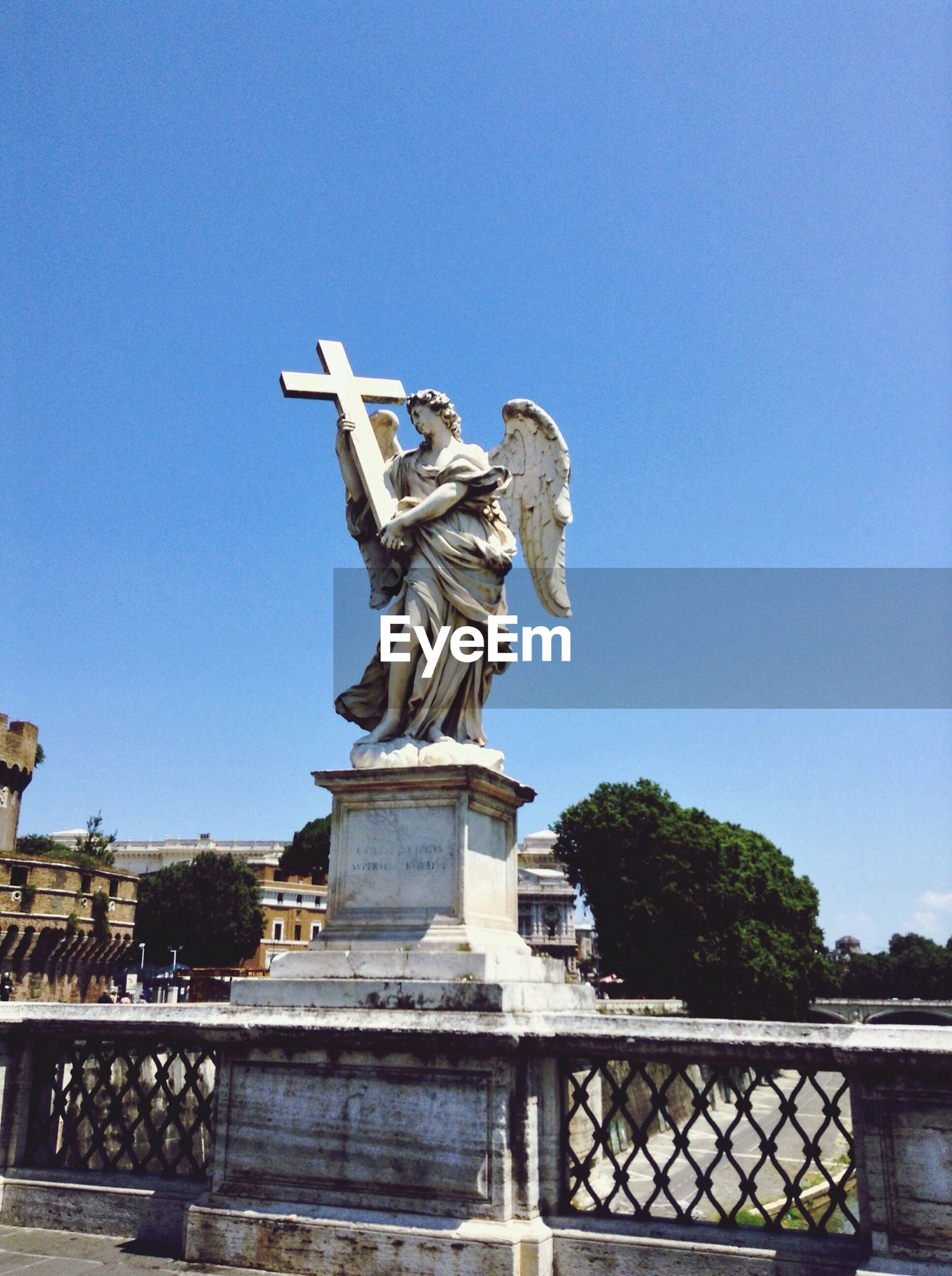 Statue of angle carrying cross on bridge balustrade