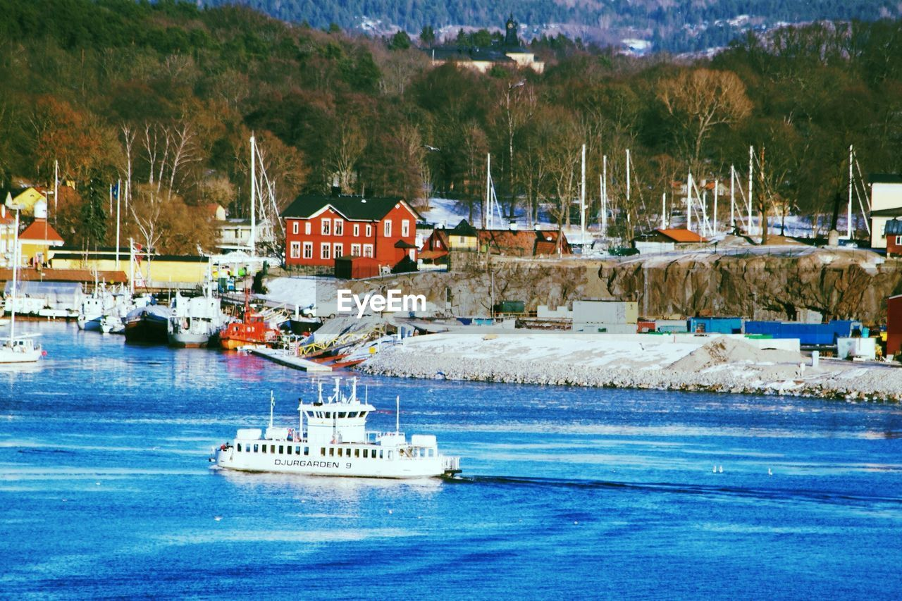 water, nautical vessel, waterfront, built structure, outdoors, tree, building exterior, day, architecture, transportation, harbor, moored, mountain, no people, nature, sea, sky