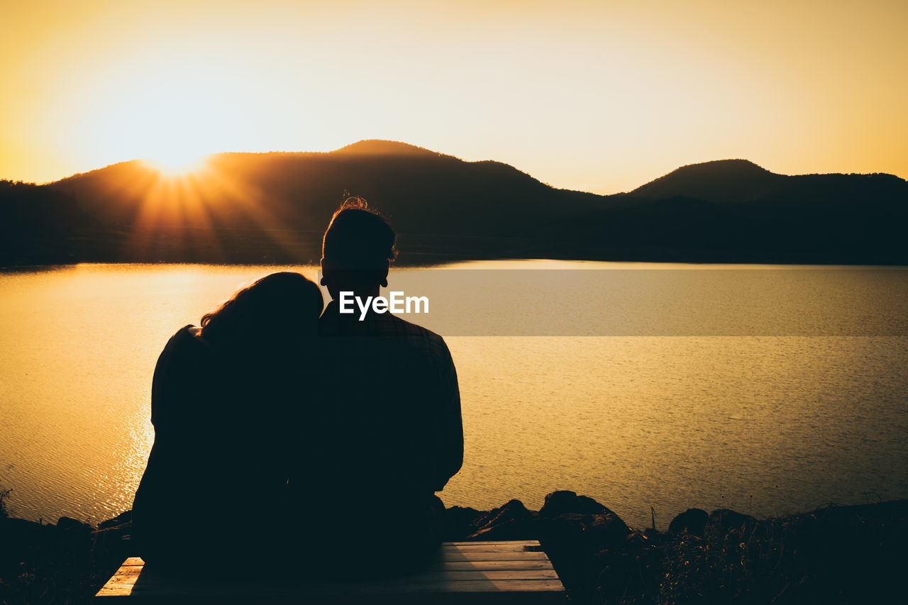 Rear View Of Silhouette Couple Sitting By Lake Against Sunset Sky