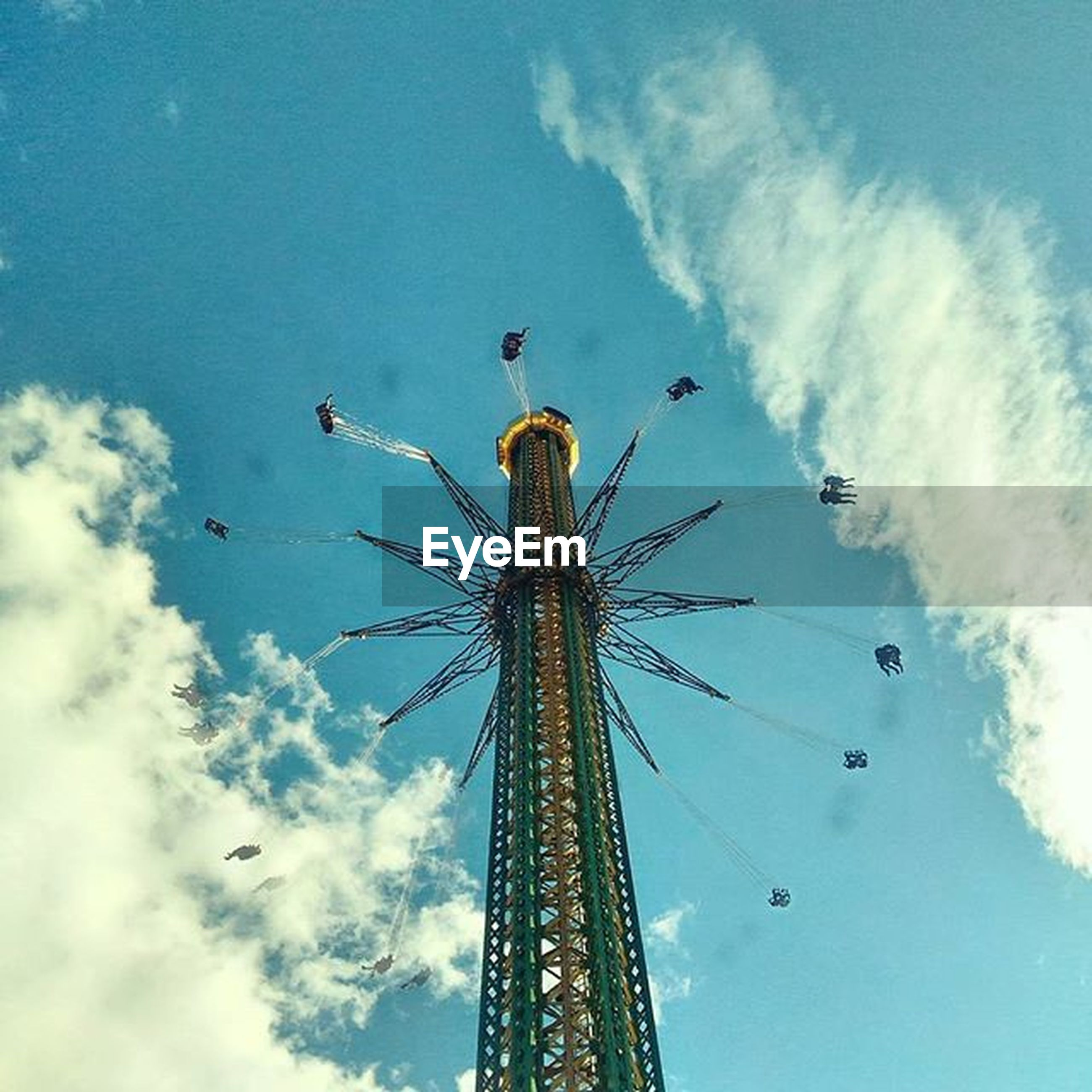low angle view, amusement park, amusement park ride, arts culture and entertainment, sky, ferris wheel, cloud - sky, chain swing ride, fun, enjoyment, built structure, cloudy, tall - high, cloud, architecture, leisure activity, fairground ride, traveling carnival, outdoors, blue