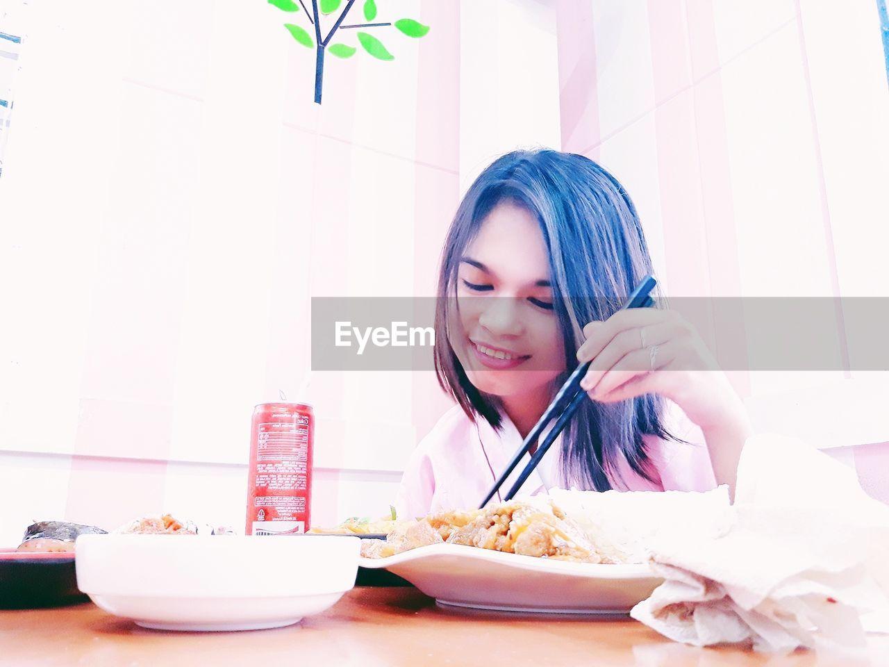 Young Woman Having Food At Table