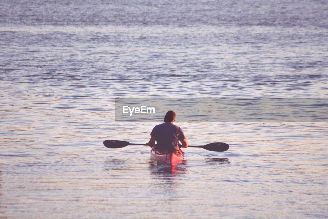 Rear View Of Man Kayaking In Sea