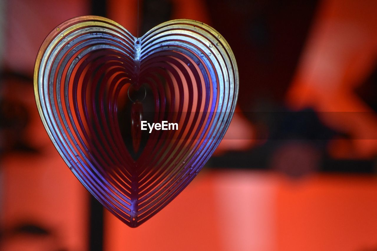 focus on foreground, close-up, heart shape, indoors, positive emotion, love, no people, pattern, emotion, design, creativity, shape, spiral, red, multi colored, selective focus, illuminated, decoration, art and craft, still life, valentine's day - holiday