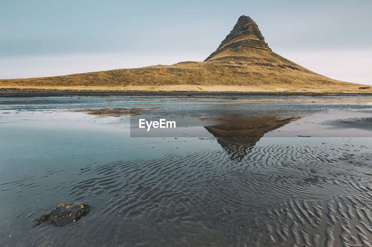 Reflection of mountain in sea against sky