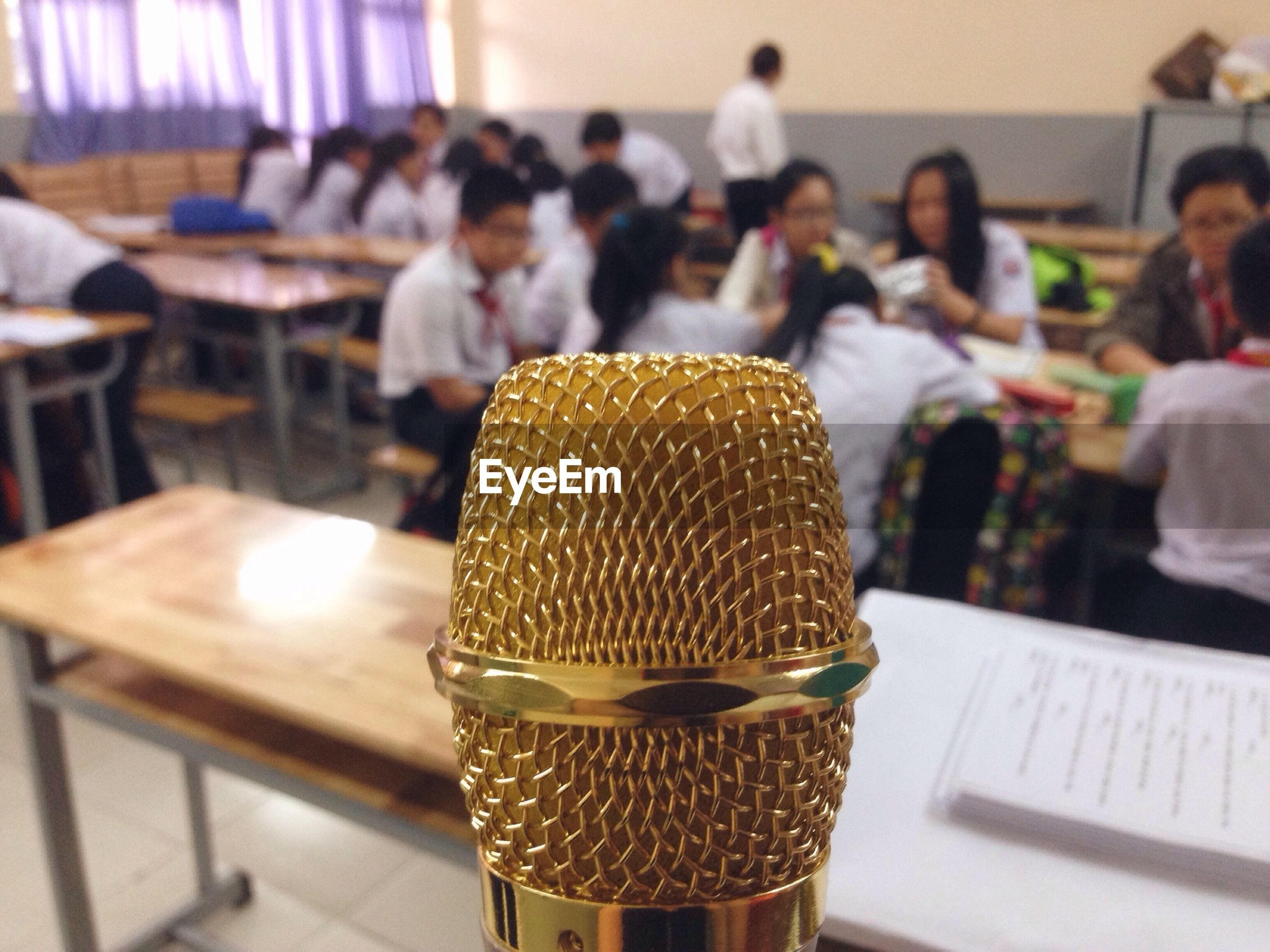 Close-up of gold colored microphone in classroom