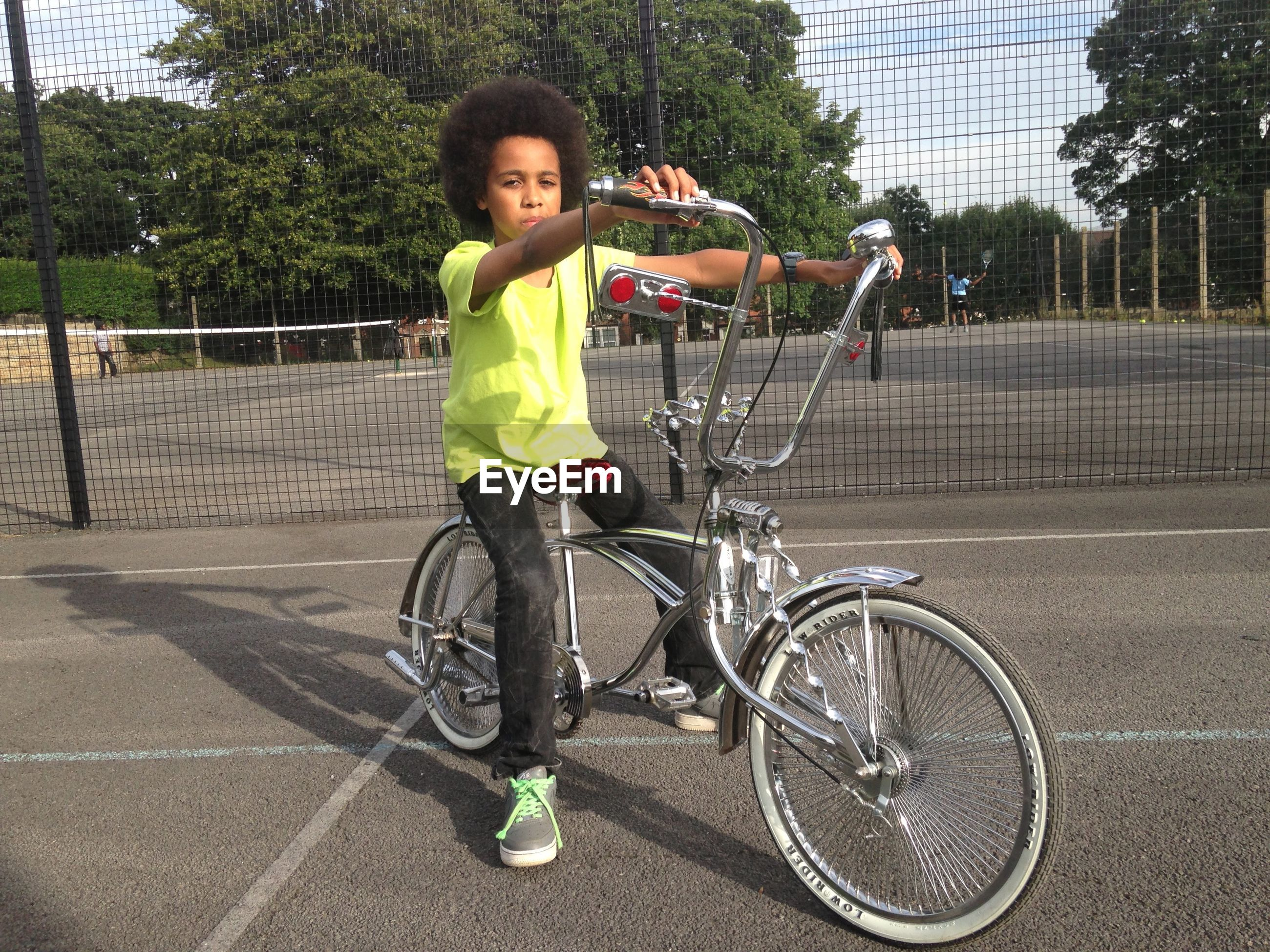 Full length portrait of boy sitting on bicycle at tennis court