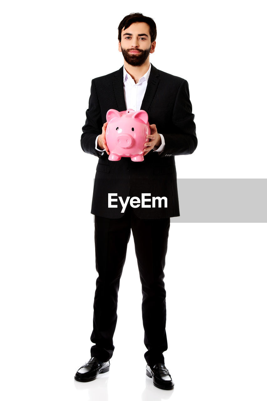 Portrait of businessman holding piggy bank against pink background