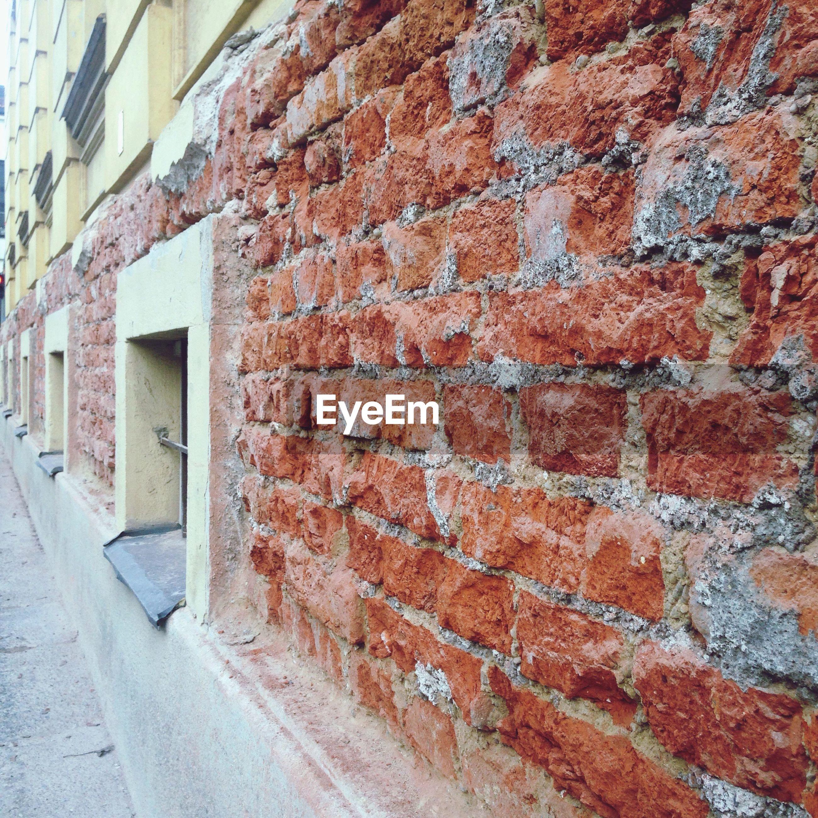 Brick wall by walkway