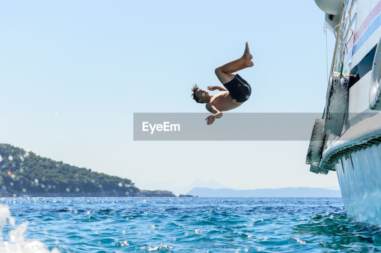 Teenage Boy Diving Into Sea Against Clear Sky