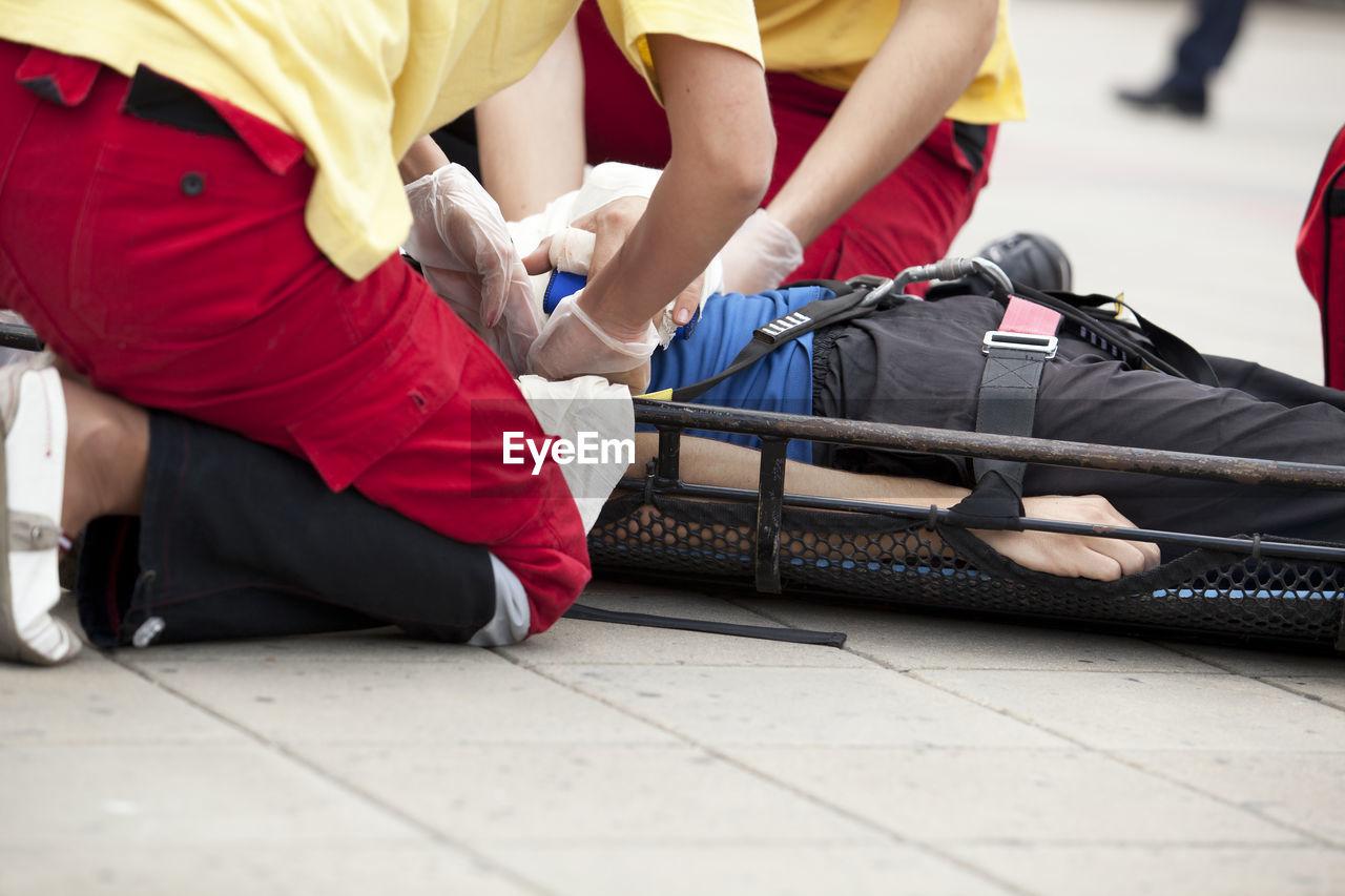 Paramedics Providing First Aid To Injured Man