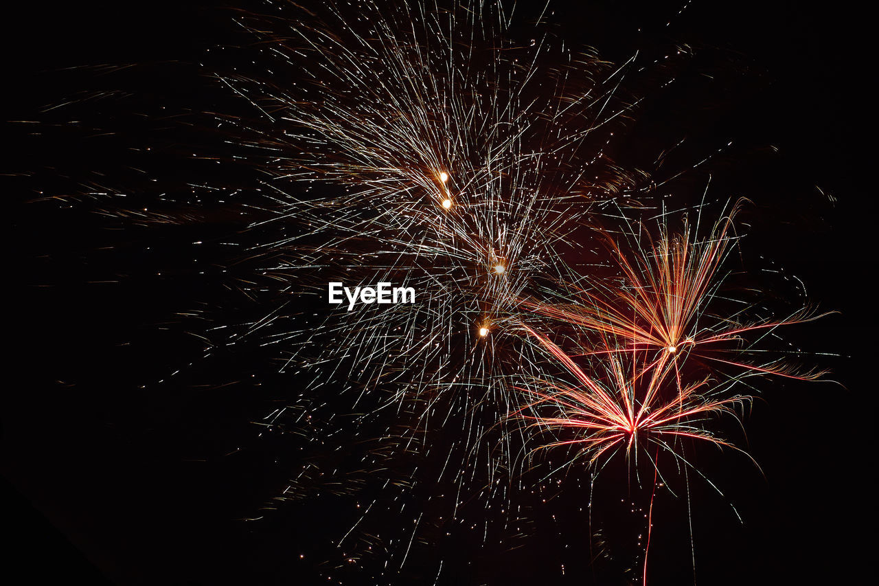 firework display, firework - man made object, exploding, celebration, night, sparks, long exposure, arts culture and entertainment, motion, event, glowing, low angle view, illuminated, no people, blurred motion, smoke - physical structure, firework, sky, outdoors