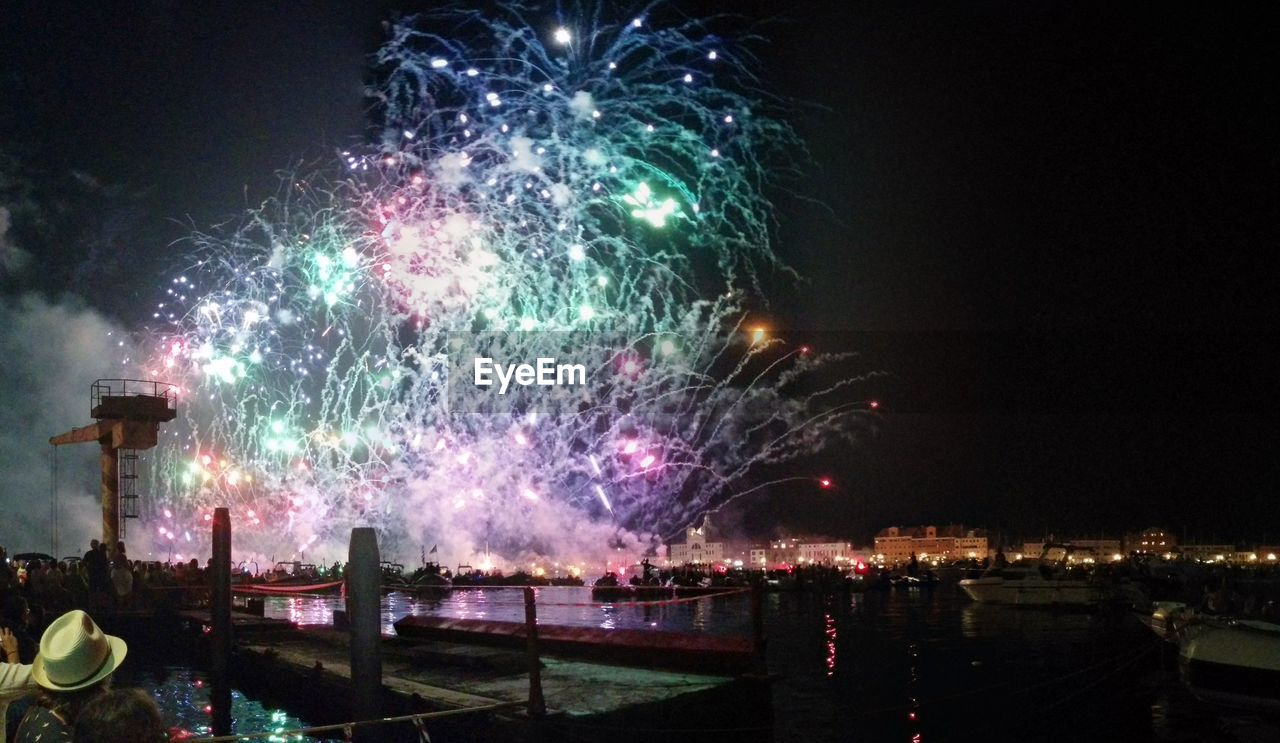 night, celebration, firework display, firework - man made object, illuminated, exploding, event, arts culture and entertainment, long exposure, sky, multi colored, outdoors, low angle view, firework, motion, no people, building exterior, architecture, city, cityscape