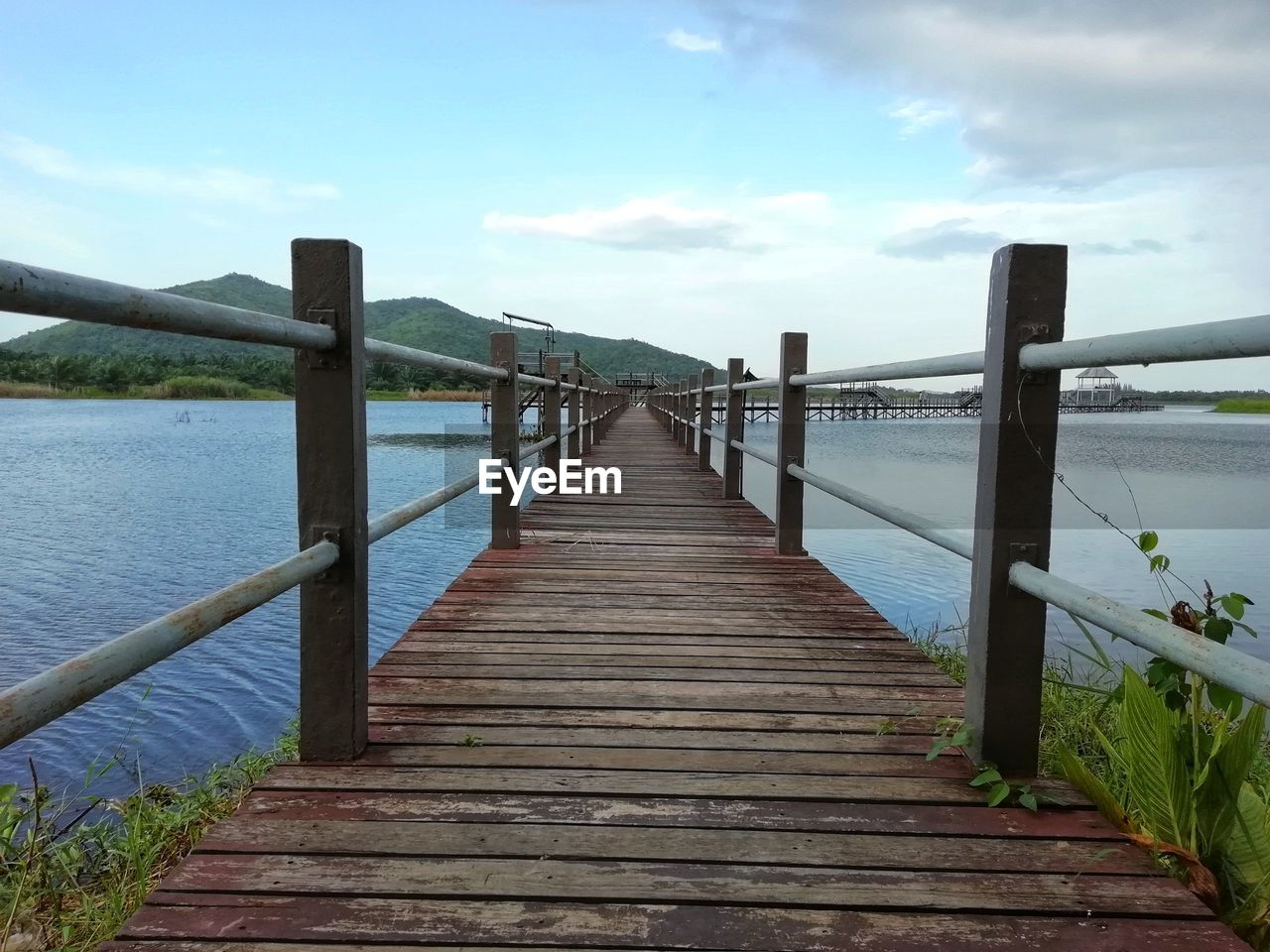 sky, water, wood - material, direction, the way forward, railing, tranquility, nature, tranquil scene, cloud - sky, pier, beauty in nature, scenics - nature, built structure, day, sea, no people, architecture, wood, diminishing perspective, wood paneling, outdoors, long