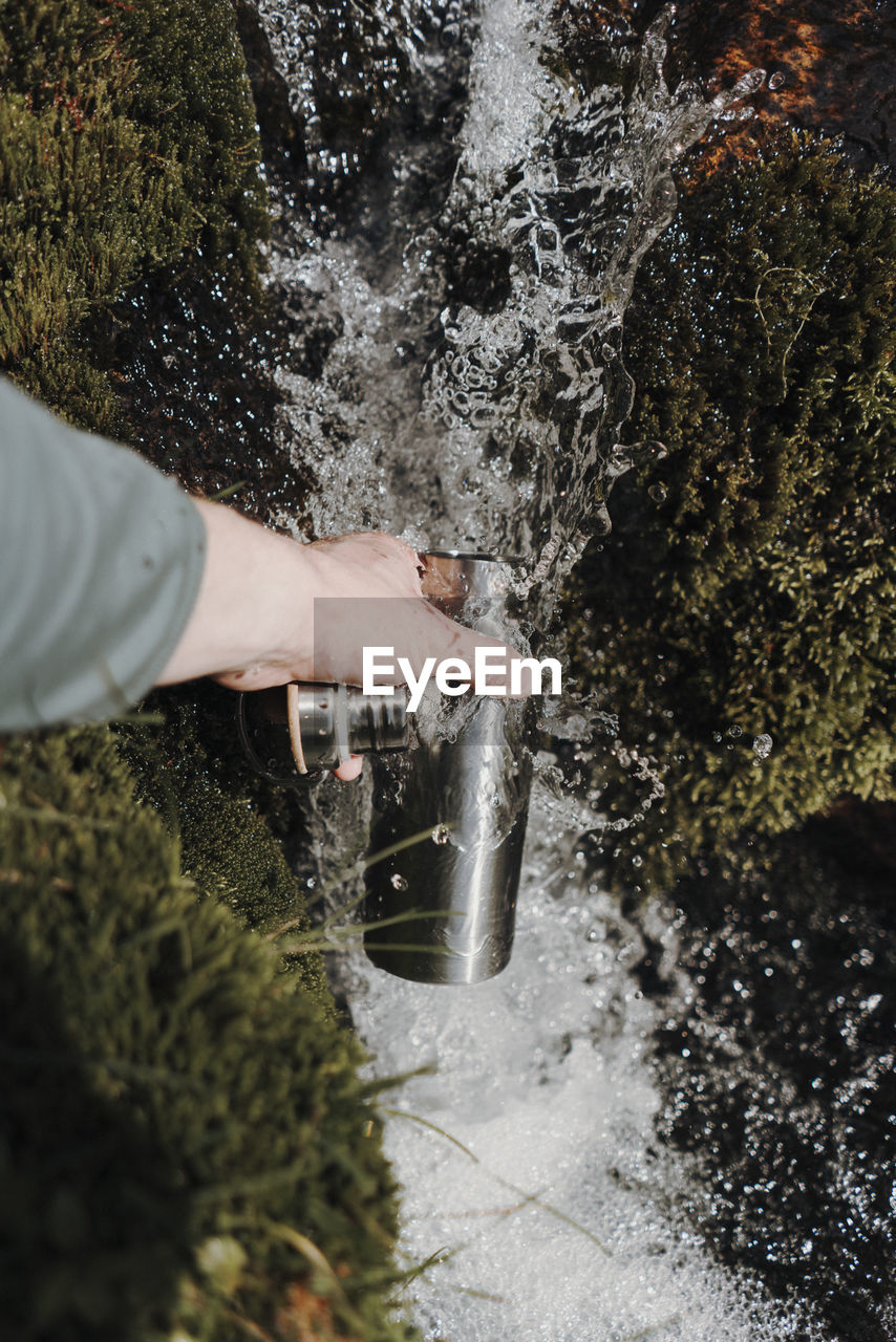 High angle view of person hand holding bottle in waterfall by rock