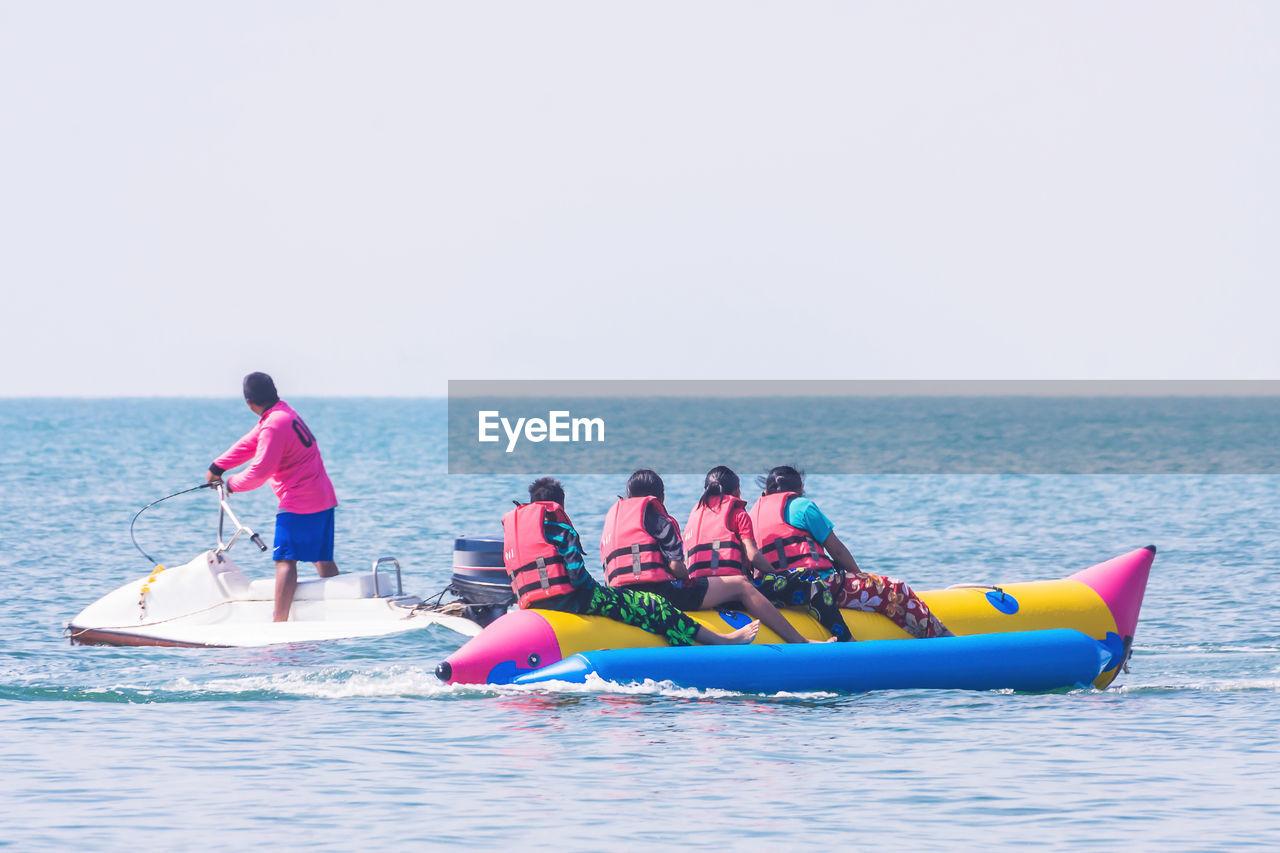 Man on jet boat by women rafting in sea