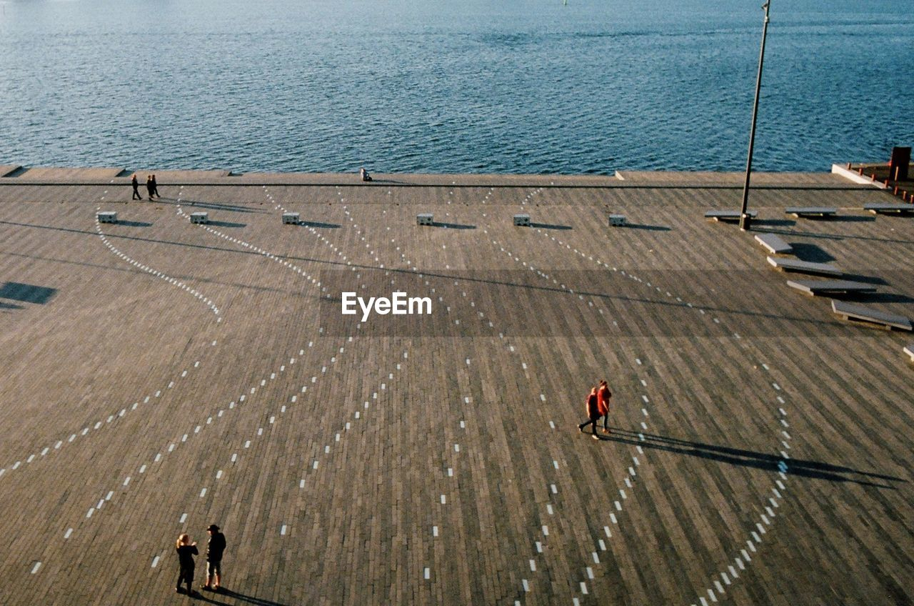 High angle view of people walking against the sea