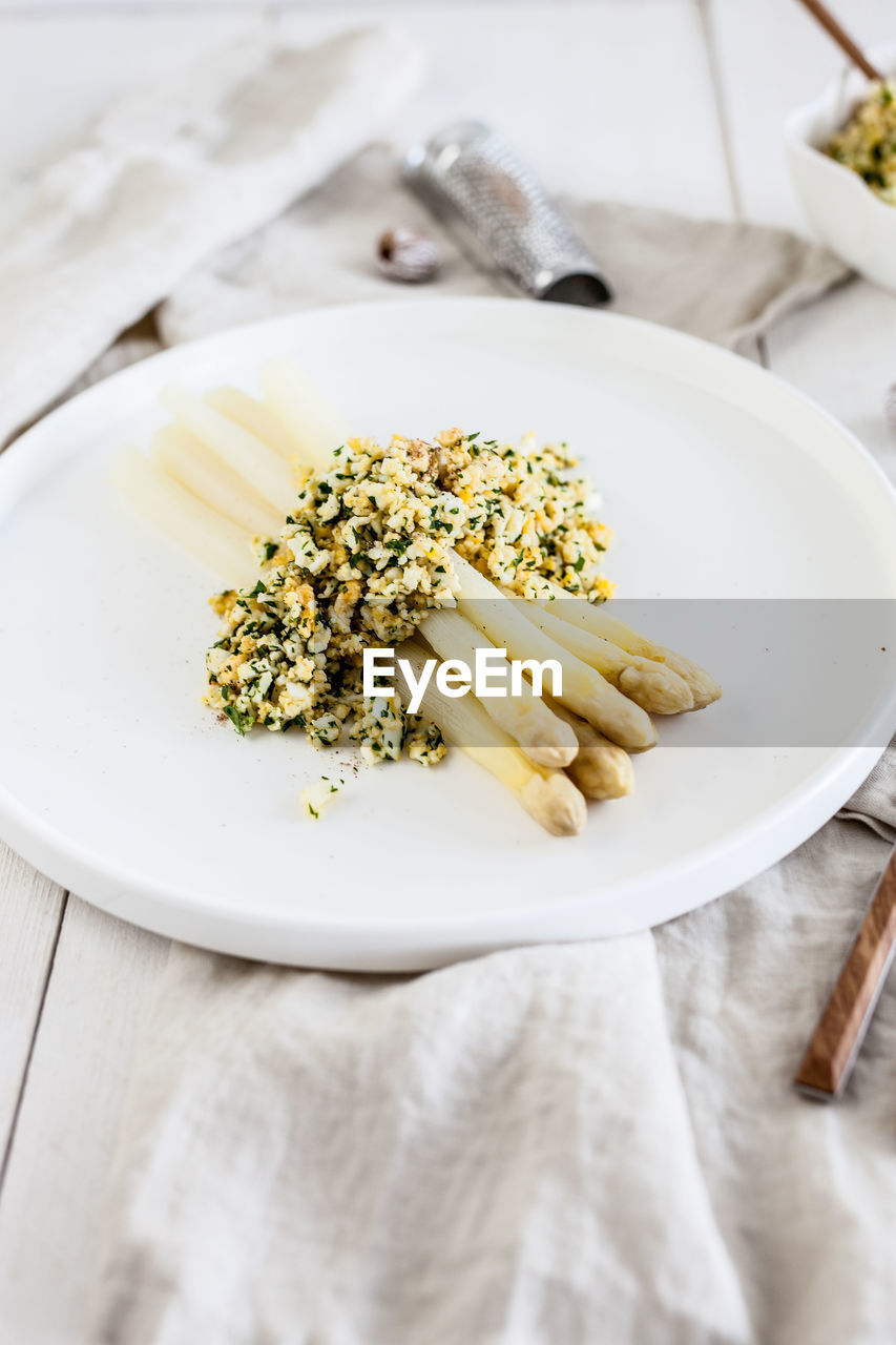 food and drink, freshness, food, table, plate, indoors, ready-to-eat, pasta, no people, wellbeing, healthy eating, still life, italian food, high angle view, close-up, white color, eating utensil, indulgence, meal, focus on foreground, temptation, herb, garnish, crockery
