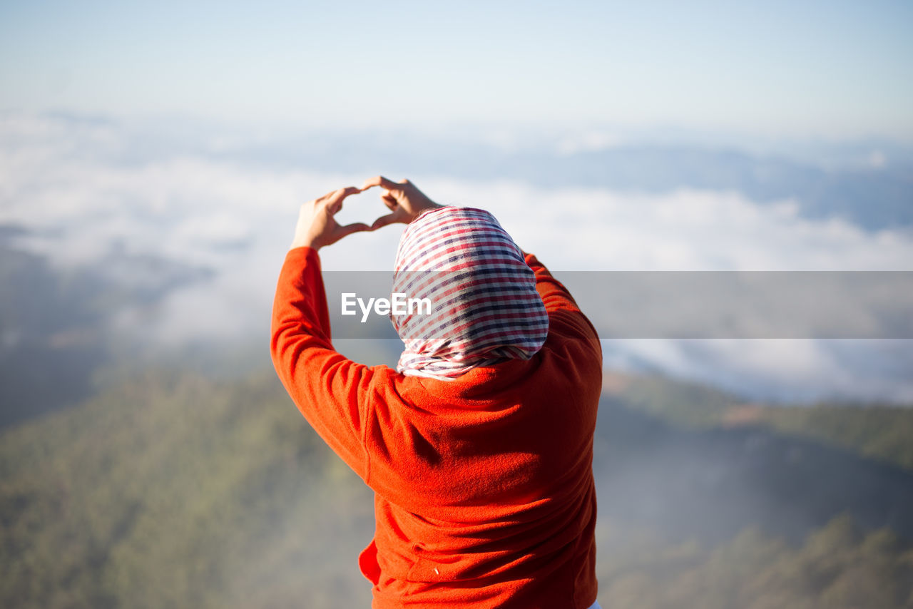 Rear view of woman making heart shape with hands against sky