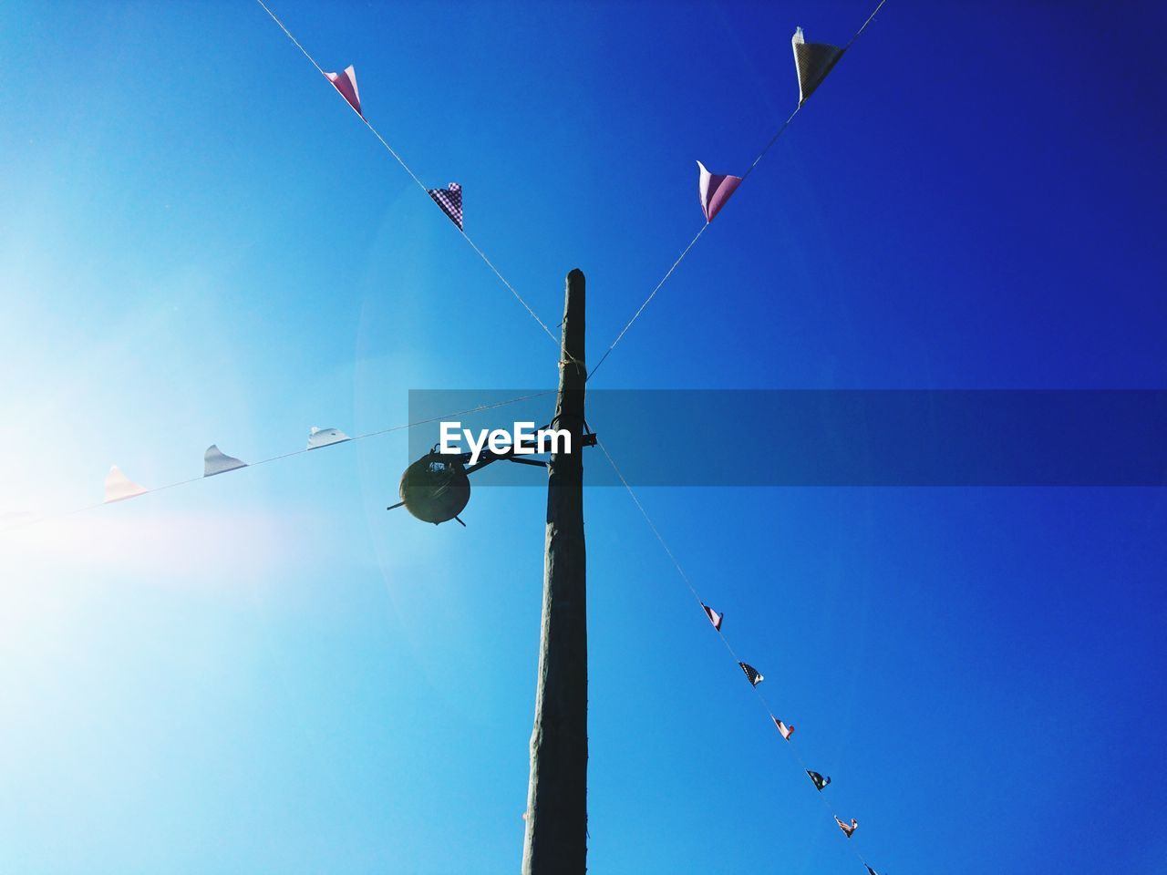 low angle view, sky, blue, nature, day, no people, clear sky, celebration, hanging, outdoors, sunlight, flag, decoration, animal, copy space, pole, animals in the wild, animal themes, cable, group of animals