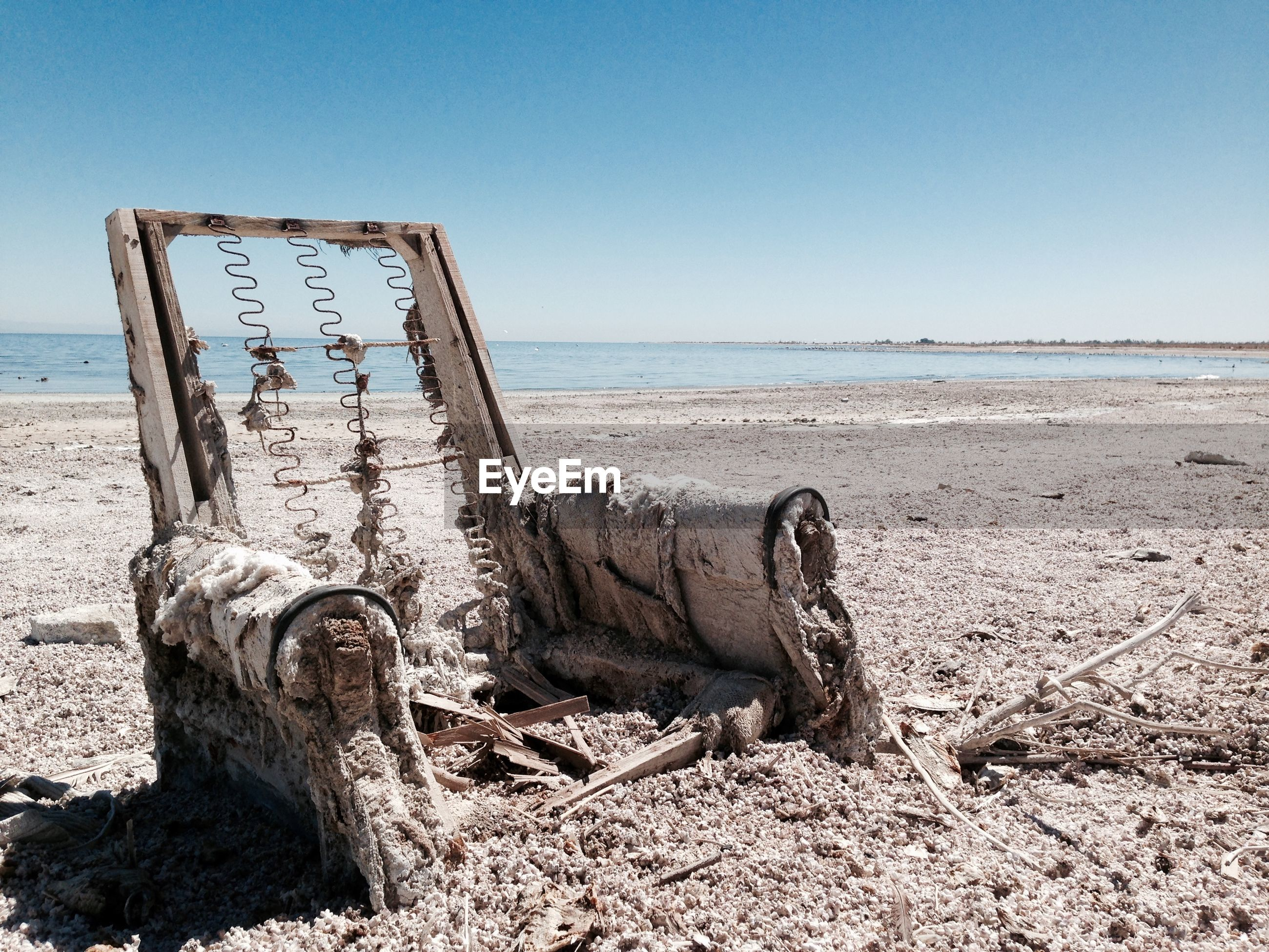 Abandoned weathered armchair at beach against sky