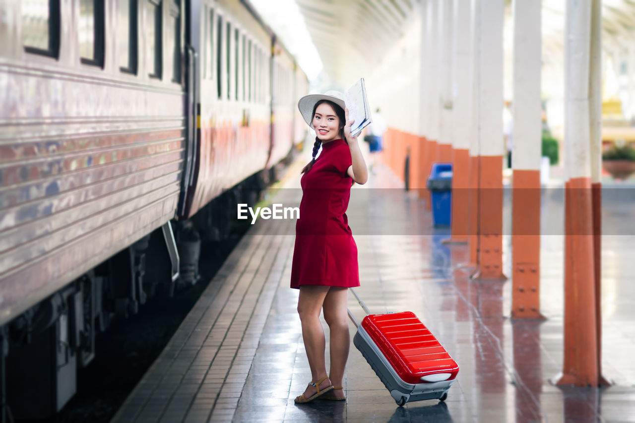 Portrait of smiling woman with suitcase walking by train at railroad station platform