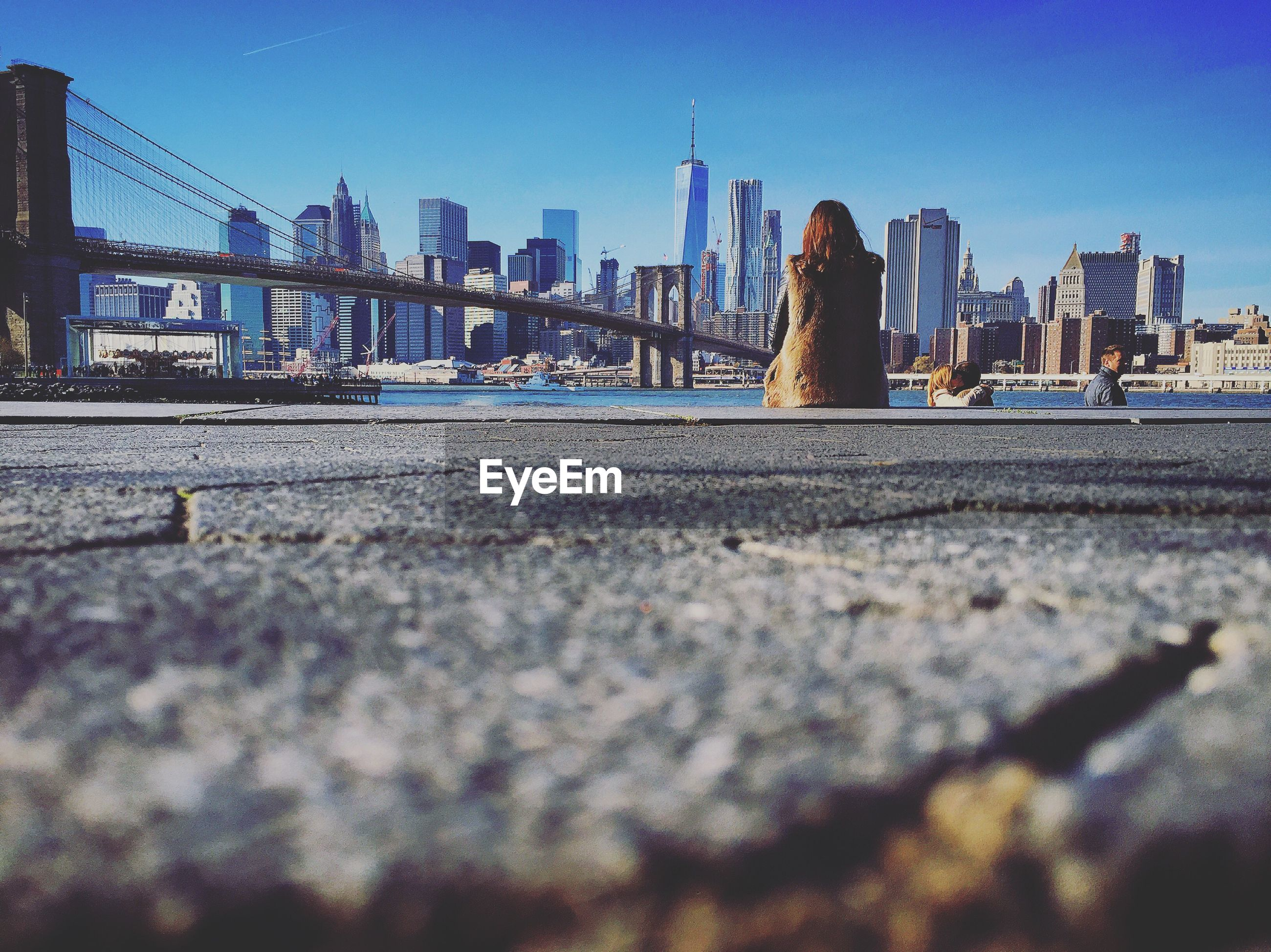 Rear view of woman sitting by brooklyn bridge and city skyline against clear blue sky