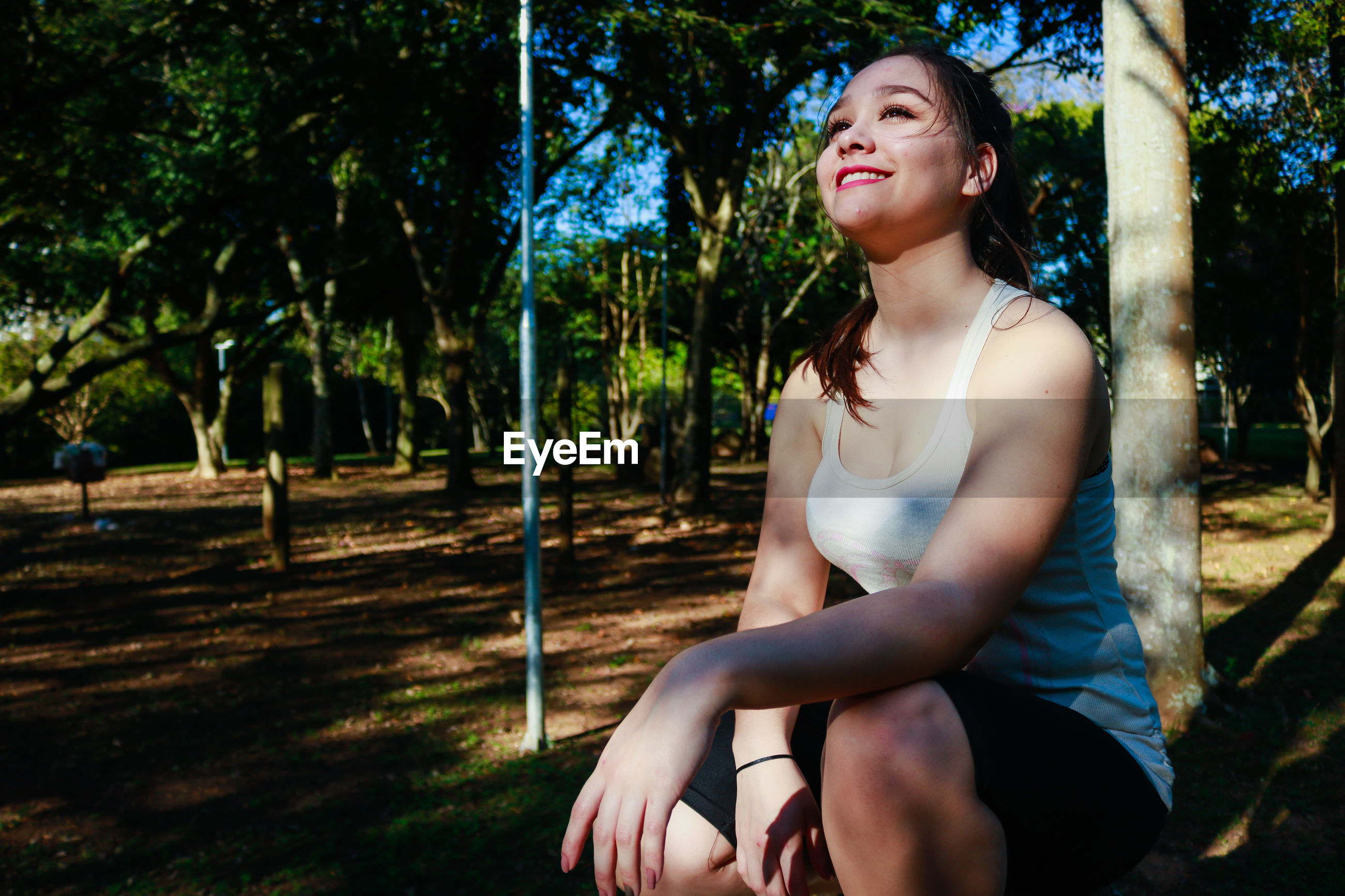 Beautiful woman smiling while crouching against tree at park