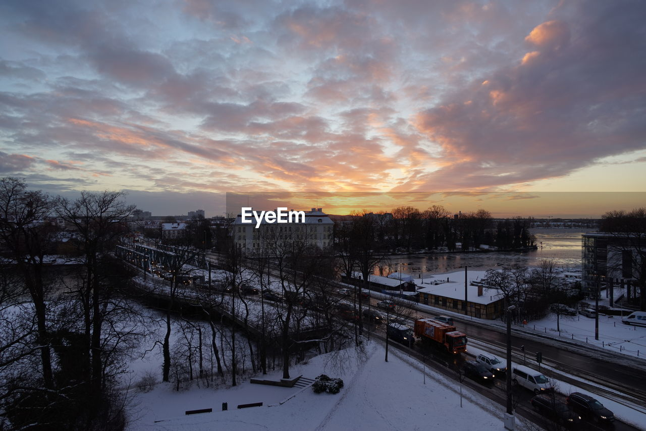 High Angle View Of Vehicles On Bridge Over Frozen River Against Sky During Sunset