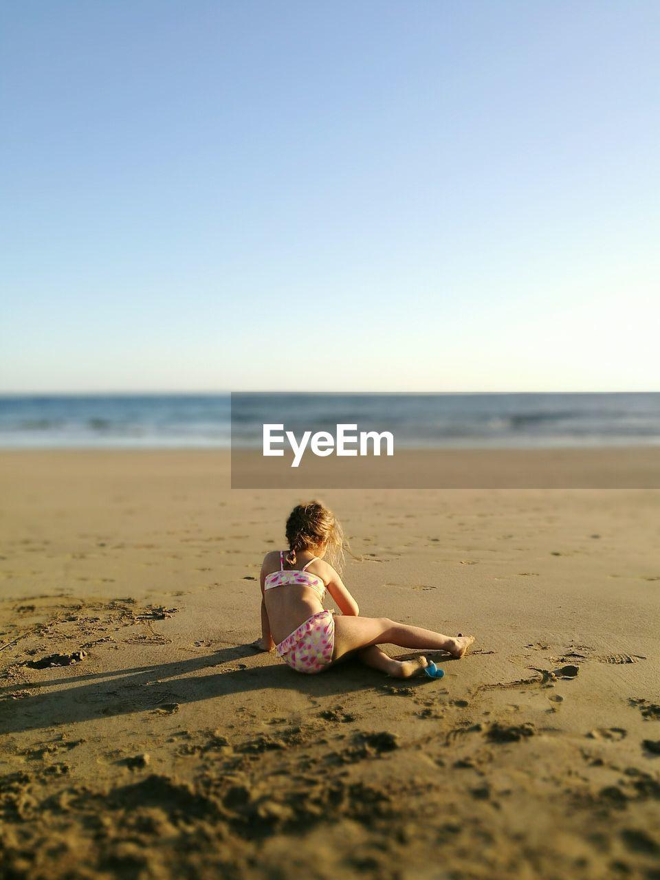 Full Length Of Girl Sitting On Beach Against Sky