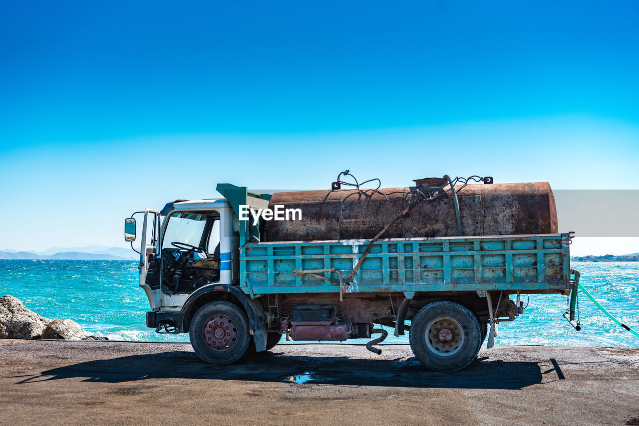 mode of transportation, transportation, sky, land vehicle, blue, day, nature, sunlight, land, clear sky, copy space, outdoors, scenics - nature, no people, truck, water, travel, motor vehicle, landscape