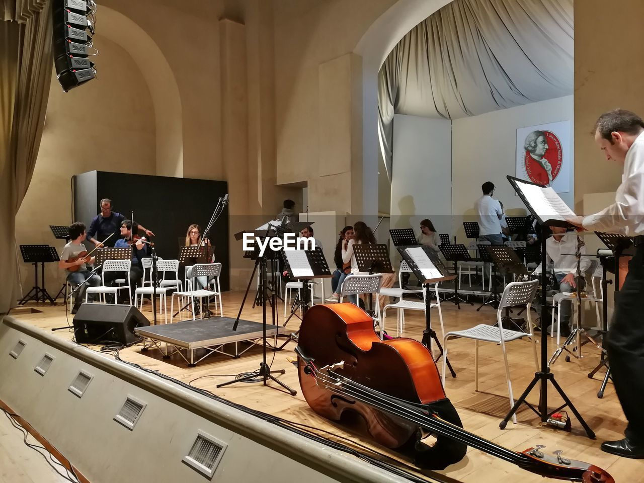 musical instrument, group of people, music, arts culture and entertainment, musical equipment, artist, men, real people, occupation, performance, musician, string instrument, sitting, indoors, group, large group of people, women, sheet music, crowd, stage, orchestra, entertainment occupation