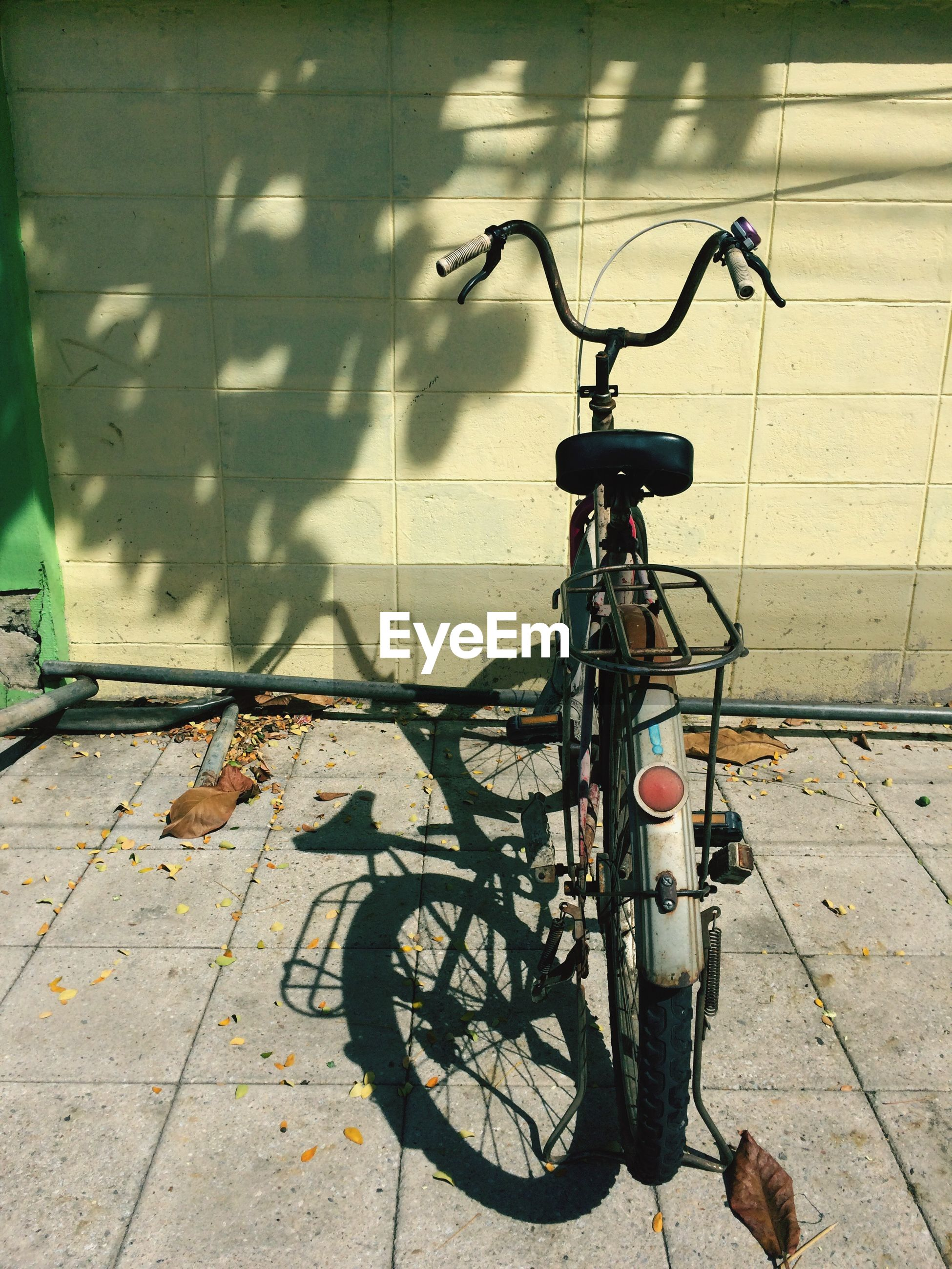 Bicycle parked against wall on sunny day