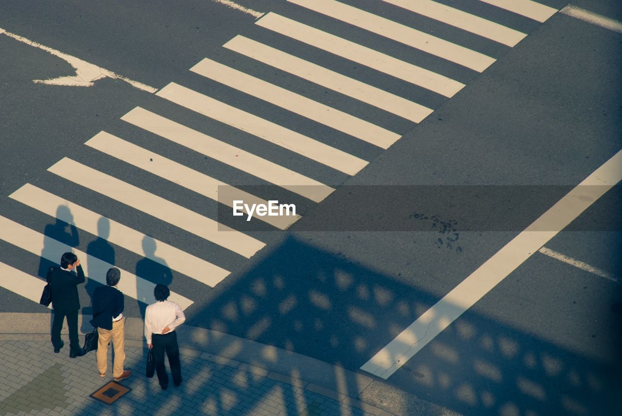 High Angle View Of Businessmen Standing On Road