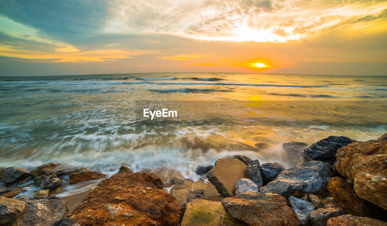 sunset, water, sea, sky, beauty in nature, scenics - nature, rock, solid, cloud - sky, rock - object, horizon over water, beach, motion, horizon, orange color, nature, land, idyllic, tranquility, no people, outdoors, flowing water, breaking, rocky coastline