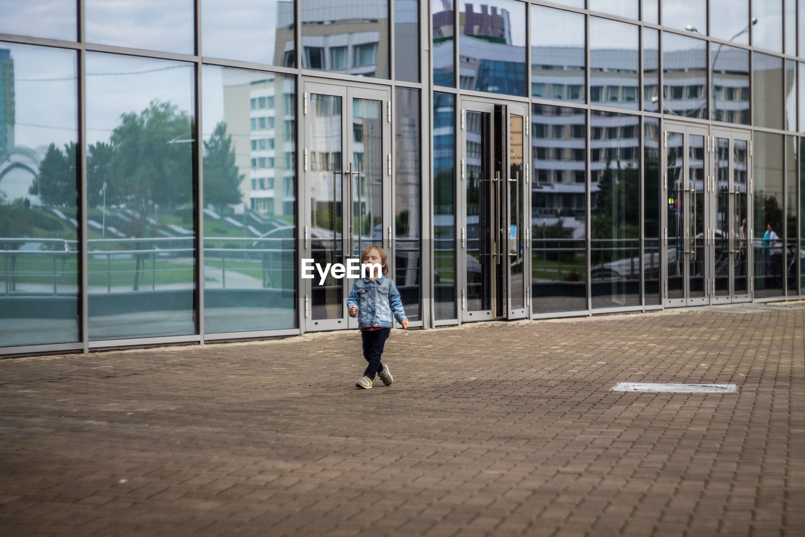 Girl walking on footpath by glass building