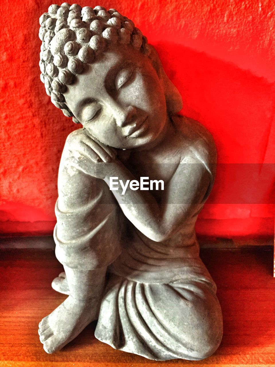 Statue Of Buddha On Table Against Red Wall