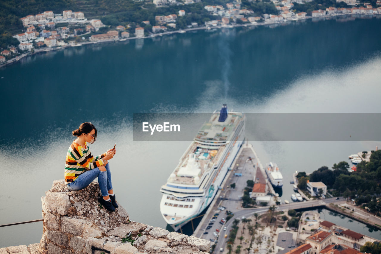 Side View Of Mid Adult Woman Using Mobile Phone While Sitting On Rock Against Sea